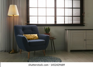 Stylish living room interior with comfortable armchair and window blinds