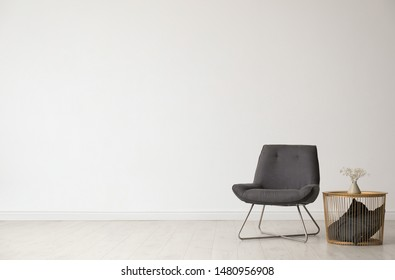 Stylish living room interior with comfortable chair and side table near white wall. Space for text