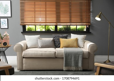 Stylish living room interior with comfortable sofa near window