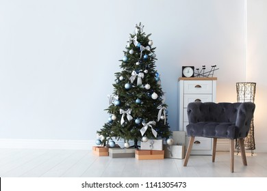 Stylish living room interior with decorated Christmas tree and comfortable armchair