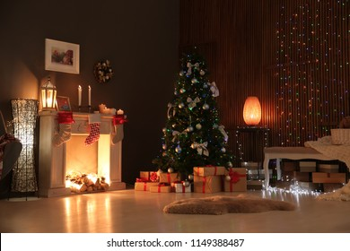 Stylish living room interior with decorated Christmas tree at night
