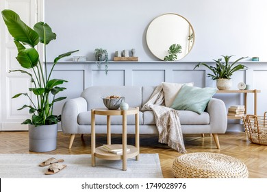 Stylish living room interior with design grey sofa, coffe table, pouf, basket, shelf, mirror, tropical plants, decoration, carpet, pillows and elegant personal accessories in modern home decor. - Shutterstock ID 1749028976