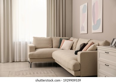 Stylish living room interior with modern comfortable sofa and pictures