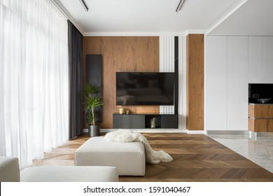 Stylish living room with wooden wall and floor and big tv screen open to kitchen with marble floors