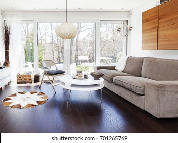 stylish living-room with dark floor and glass doors out to the garden