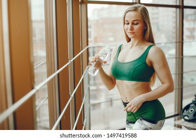 A stylish long-haired girl wearing a green sports suit standing near a large window in the gym and drinking near water