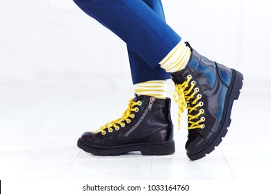 stylish look of patent leather ankle boots with yellow shoelaces and socks at young boy