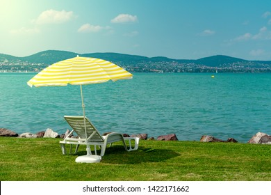 Stylish lounger plastic sunbed with yellow stripes sunshade beach umbrella on the green grass on beach at summer under open sky. Sunbed at Lake Balaton Hungary