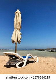 Stylish lounger in yellow sand to sun sunbed on beach in summer under open sky. Sunbed intended for cold shadow on convenient lounger. Fashion lounger with umbrella, plastic sunbed during hot weather.
