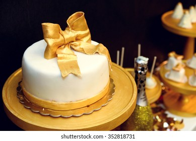 stylish luxury decorated candy bar with frosting cake and champagne at the golden birthday party, holiday celebration concept