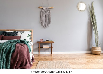 Stylish and luxury interior of bedroom with design furnitures, palm leaves, night table, gray macrame on the walls and elegant accessories. Beautiful bed sheets, blankets and pillows. Warm home decor.