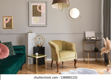Stylish and luxury living room of apartment interior with elegant green velvet armchair and sofa, retro table, marble stands, design lamps, chic accessories. Mock up frames on the molding gray wall.