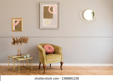 Stylish and luxury living room of apartment interior with elegant green armchair, retro tables, design lamps, chic accessories and gold mirror. Mock up frames on the molding gray wall. Home decor.