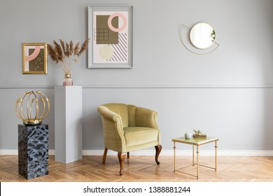 Stylish and luxury living room of apartment interior with elegant green armchair, retro table, marble stands, design lamps, chic accessories and gold mirror. Mock up frames on the molding gray wall.