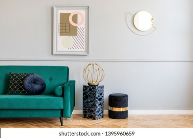 Stylish and luxury living room of apartment interior with elegant green sofa, retro lamp, marble stands, design pouf, chic accessories and gold mirror. Mock up frames on the molding gray wall. Home.