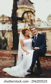 stylish luxury red haired bride and elegant groom, sitting in the autumn park, on the background of the old city Lviv