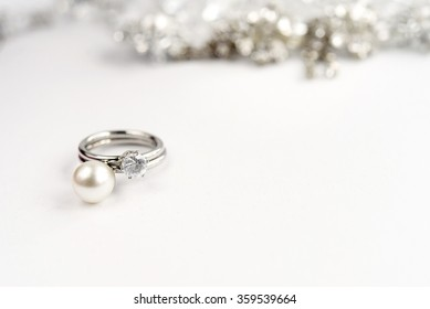 stylish luxury rings with pearl and diamond on white background, space for text, love gift concept