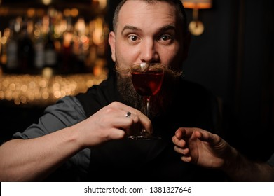 Stylish male bartender with beard and styled mustache sips an alcohol cocktail in bar