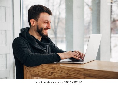 Stylish male freelancer working on new startup project making internet researchers analyzing data using laptop computer
