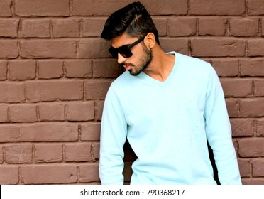 Stylish male model having glasses in front of brick wall