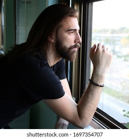 Stylish male model with long hair and beard looking through window. Self isolation at home. Boredness, police hour due to Corona virus. Quarantine, Covid-19 concept.