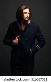 Stylish male model with long hair wearing classic fashionable blue jacket