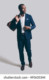 Stylish man with bag. Full length of handsome young African man in full suit carrying brown leather bag on shoulder and looking away while standing against grey background