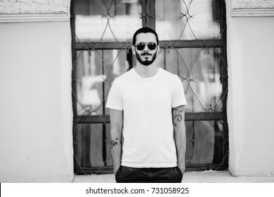 A stylish man with a beard cleans his glasses with a T-shirt. Street photo