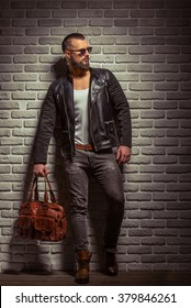 Stylish man with beard in leather jacket and sunglasses holding a brown leather bag, standing against brick wall