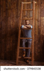 Stylish man with beard in striped vest leaning on a ladder, looking at camera, standing on a wooden background