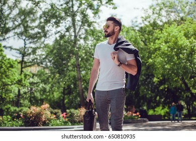 Stylish man with a beard and in sunglasses stands on the street with a bag in his hands.