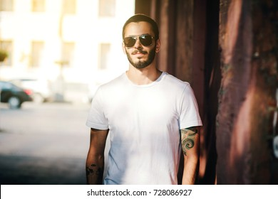 A stylish man with a beard in a white design T-shirt and glasses on a city background. Street photo