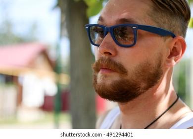 Stylish man, bearded portrait closeup. Outdoor summer