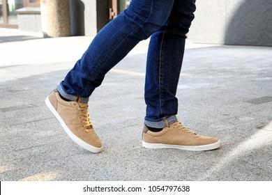 Stylish man in beige shoes walking down the street