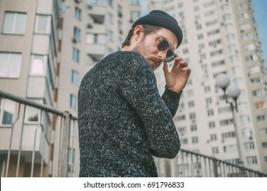 Stylish man in black glasses on skyscraper background.