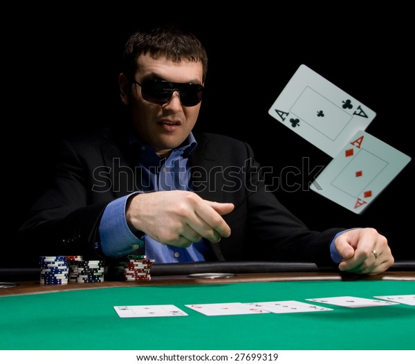 Stylish man in black suit folds two aces in casino poker at Las Vegas over black