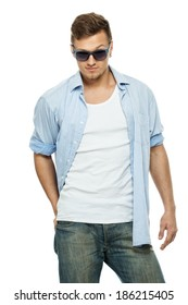 Stylish man in blue shirt and jeans wearing sunglasses isolated on white