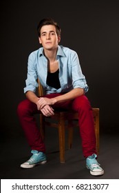 Stylish man in blue shirt and red jeans, sitting on a chair. Studio shot