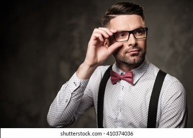 Stylish man with bow tie wearing suspenders and posing on dark background.