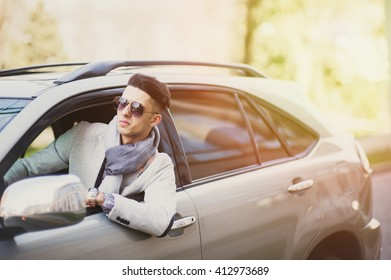 Stylish man in the car cursing someone with a menacing look
