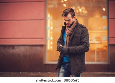 stylish man in a coat with a smartphone in the city. traveling