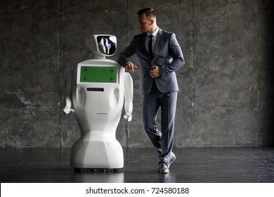 A stylish man communicates with a robot. Cybernetic system today. Modern Robotic Technologies. Humanoid autonomous robot. loft office
