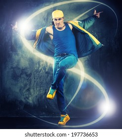 Stylish man dancer showing break-dancing moves with magic beams around him