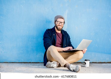 Stylish man dressed casual in sweater and hat working with laptop sitting near the blue wall background