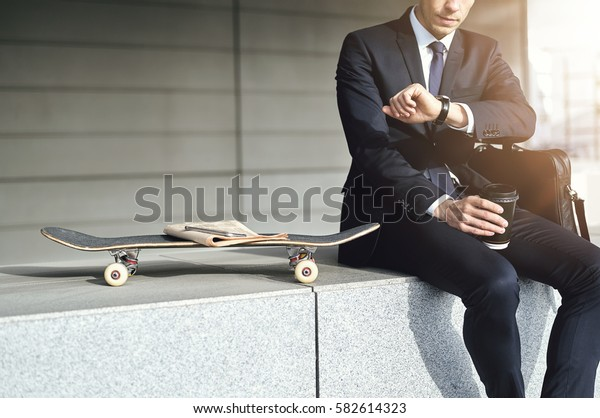 Stylish man drinks coffee and looking at his watch. Horizontal outdoors shot