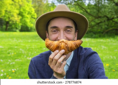 Stylish man eating a croissant outdoors