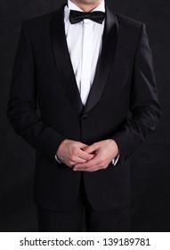 Stylish man in elegant black tuxedo, on black background