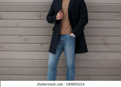 Stylish man in elegant fashionable black coat in a vintage knitted sweater in stylish jeans near a wooden wall. Spring collection of fashionable men's clothing. Close-up.