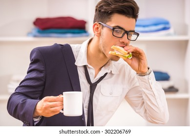 Stylish man in glasses eating his breakfast while hurring to work.