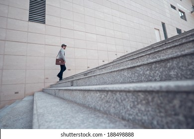 Stylish man going up the stairs, view from the side